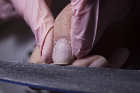 Master of manicure and saws nails with a nail file. Giving a square shape to the nails. Professional manicure in the salon close-up.