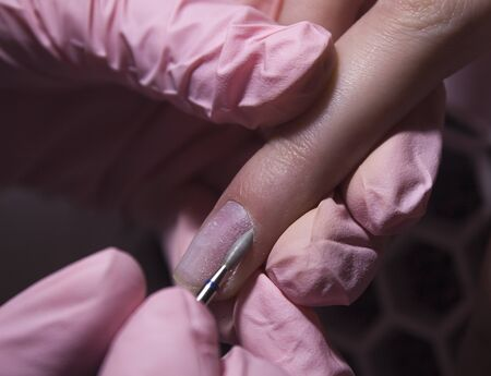 The manicurist cleans the cuticle of the nails with the device. Cuticle removal using a machine with a cutter. Professional manicure in the salon close-up.