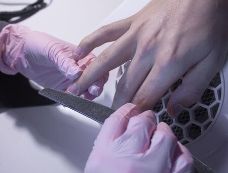Mens manicure in the salon. The master makes a manicure for a man. A manicurist saws a mans nails with a nail file. Alignment of nails with a nail file. Reklamní fotografie