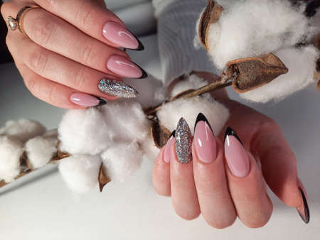 Hands with long pink nails hold a sprig of cotton. Black french manicure with silver glitter design. Female fingers with beautiful nails