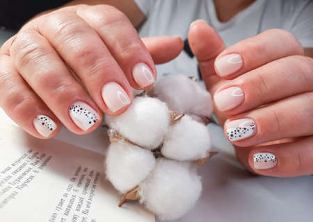 Soft pink gel polish with a design of black dots on the background of the text of the book. Women's hands with pastel colored nails hold a sprig of cotton. Milk manicure with black and white design. Stock Photo