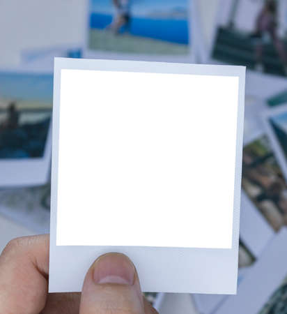 A person holds a photo in his hands against the background of other photos. Photo in hand close-up. A person looks at a photo from a .