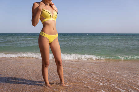 A charming sexy woman in a bikini stands with her back to the sea. Slim girl in yellow swimsuit, close-up hips with work space. A beautiful model with a good figure and legs on the ocean coast Imagens