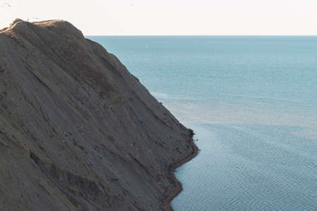 A steep cliff on the sea coast. A steep mountain on the background of a clear sky and ocean.