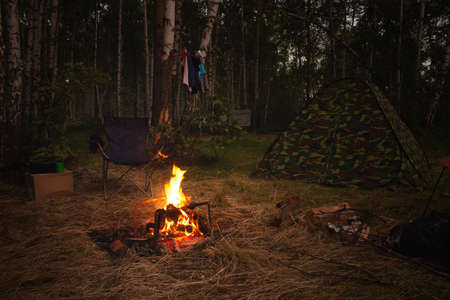Night camp in the forest with a campfire. A tent with a fire and a chair in the evening in the forest. Outdoor recreation