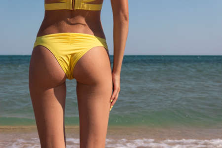 A charming sexy girl in a bikini stands with her back to the sea. Slim woman in yellow swimsuit, close-up hips with work space. beautiful female legs on the ocean coast