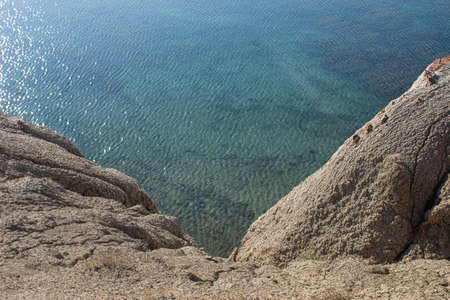 View from the mountain to the clear water in the sea. A calm black sea with a visible bottom from above.
