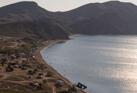 Camping on the beach. A tent city in a quiet bay on the coast and against the backdrop of mountains.