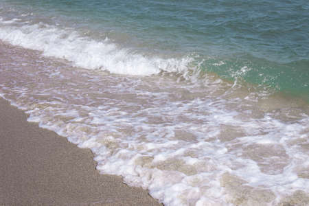 Background of a sandy beach with sea waves. Foam from a wave on the sand. A foamy ocean wave on a seashell beach