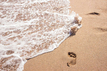 Human footprints on the sand with sea water. Foam from a wave on the sand. A foaming ocean wave washes away the traces on the shell beach