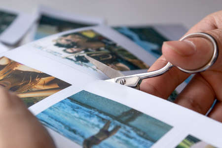 A man cuts out photos with people in close-up. A man uses scissors to cut printed photos for an album. A person holds a photo in his hands against the background of other photos. Imagens