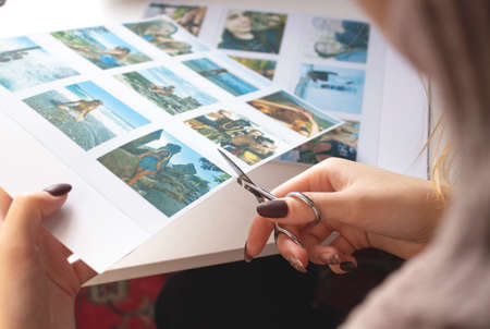 A woman cuts out photos with people in close-up. A girl uses scissors to cut printed   photos for an album. A person holds a   photo in his hands against the background of other photos.