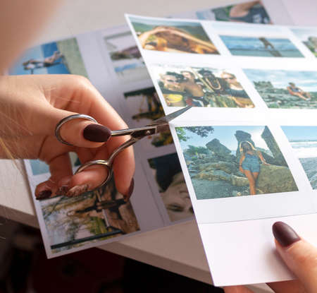 A woman cuts out photos with people in close-up. A girl uses scissors to cut printed photos for an album.