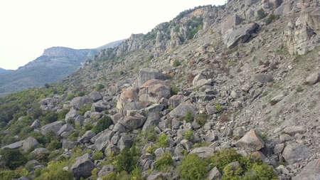 Rocky terrain. A steep rocky mountain against a clear sky. A mountain peak.