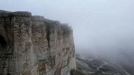 Steep cliffs with a misty gloomy sky. A thick, eerie fog hangs over the mountain and the valley.