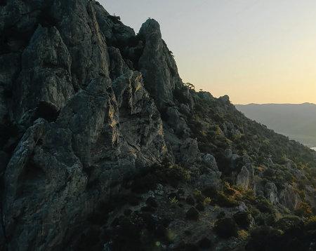 A steep cliff. A steep rocky mountain against a clear sky. A mountain peak. Imagens