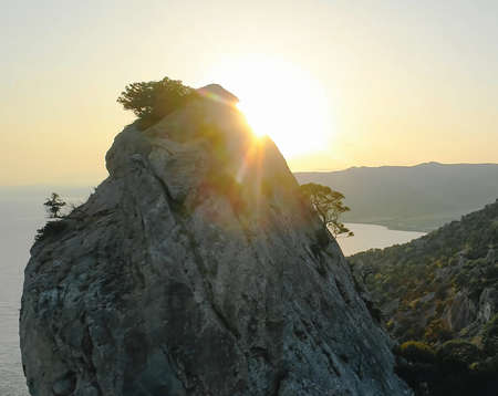A steep cliff. A steep rocky mountain against a clear sky and a sun glare. A mountain peak with growing trees. Imagens
