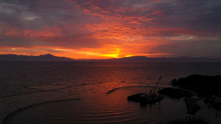 A beautiful bright red sunset. The sun goes behind the river and beyond the mountains Imagens
