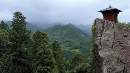 A Chinese Buddhist temple in the wooded mountains. An Asian structure on a rock against the background of gloomy cloudy mountains Imagens