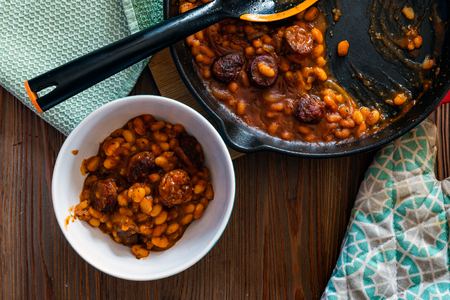 beans with sausage on a cast iron skillet