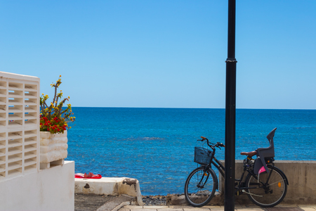 Ocean view with the bicycle with baby seat, flowers and towel with the shoe on it - Image