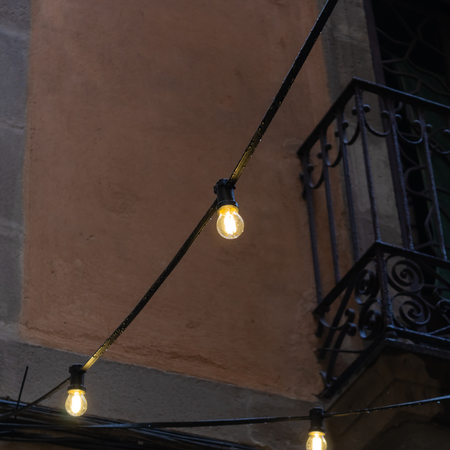 String of three bulb lights with the balcony on the background - Image Imagens