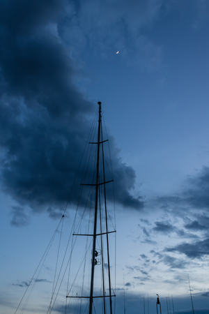 Yacht mast with the evening sky and moon - Image