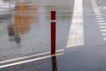 Boundary pillar on the rainy day, red traffic pole  - Image