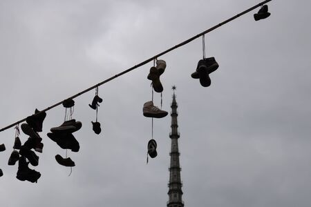 TURIN, ITALY - 25 May 2019: Shoes on the string with Mole Antonelliana on the background, Turin, Piedmont, Italy - Image