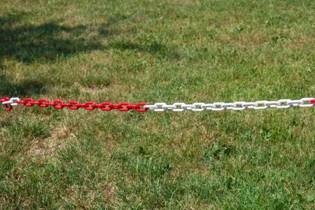 Red and white plastic chain prohibiting parking closeup - Image