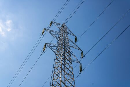High voltage pole cable wire on a sunny day with the blue sky, electricity grid - Image Imagens