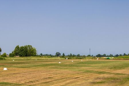The field with runway and the small aircraft, grass field runway - Image