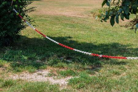 Red and white plastic chain prohibiting passage/parking, hanging on two bushes - Image