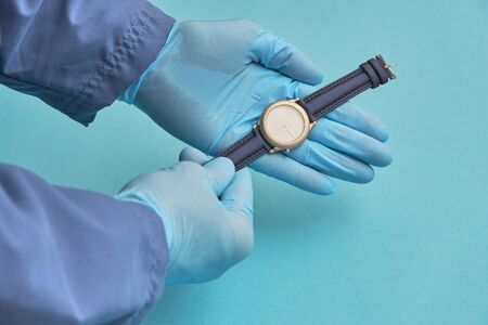 doctor in rubber gloves holds a clock. time care concept