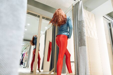 red-haired girl measures red leather pants. beautiful woman reflected in the mirror. lady buys clothes. shopaholic