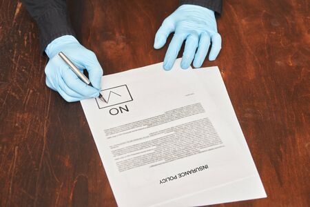 man in latex gloves signs a blank. mark not approved not agreed no. rejection concept Фото со стока