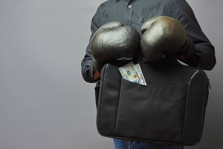 businessman in boxing gloves holds a briefcase and money in his hands. business safety concept Imagens
