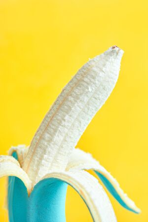 peeled dyed blue banana on a yellow background. copy space. concept design