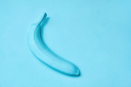 blue painted banana on the background. creative design. copy space