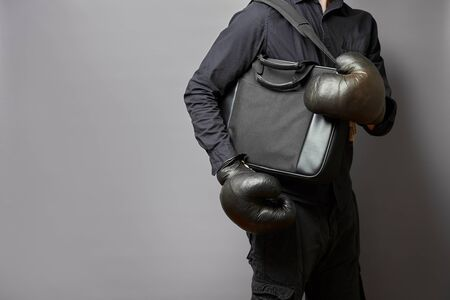 businessman in a shirt in boxing gloves holds case