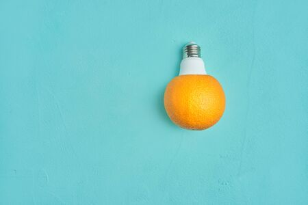 orange in a light bulb on a turquoise background. creative design concept