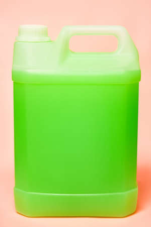 large plastic sanitizer canister. pink background. liquid soap