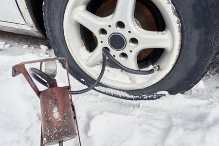 flat tire on a car in winter. old foot pump inflates the wheel