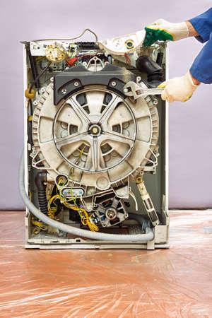 master repairs washing machine. repair of equipment with wrench