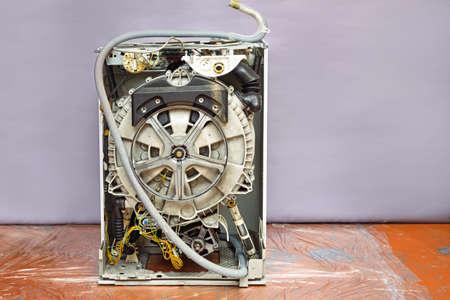 disassembled washing machine. repairs. gray background