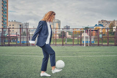 girl in an office suit hitting hitting soccer ball on the stadium field. concept