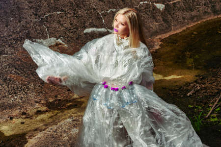 fashion creative. model posing in cellophane with plastic bottles. concept