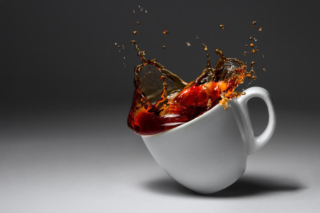 cup of coffee or tea fell illuminated surface. spilled drink Stock Photo