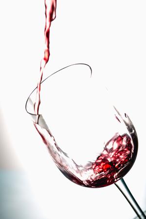 jet stream: Pouring wine into the glasses, white background, isolated Foto de archivo