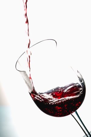 Pouring wine into the glasses, white background, isolated Stock Photo